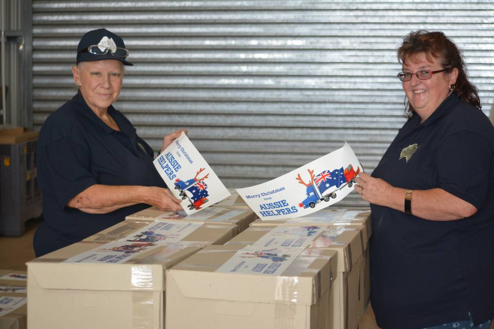 STILL GIVING: Merrilyn Mulcahy and Kelly Lovell at Aussie Helpers help pack Christmas packages for farmers in need. Photo: Daniel Shirkie.