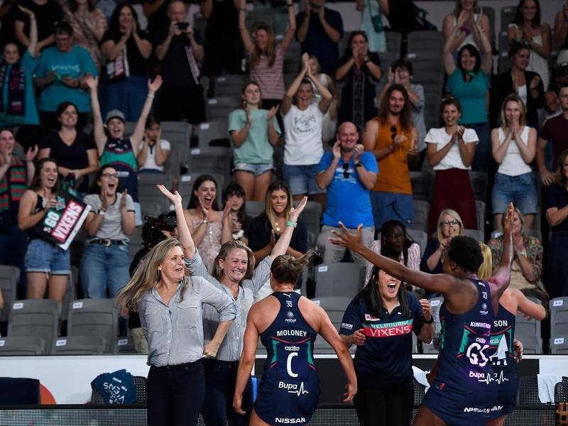 Melbourne Vixens players and staff celebrate victory in the Super netball grand final.